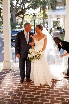 Bride in v neck lace cap sleeve Romona keveza wedding dress with white bouquet and father
