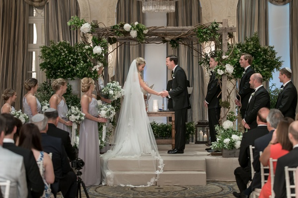 bride and groom laughing during their ceremony, indoor ceremony with wooden chuppah, cathedral veil