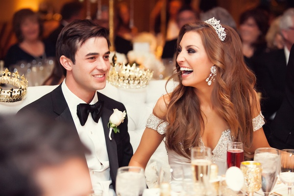 Bride and groom at sweetheart table with crowns