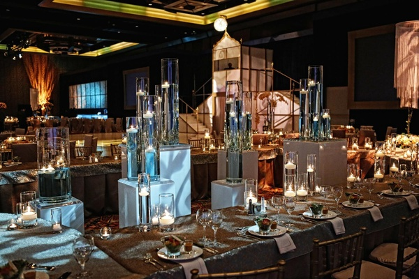 Wedding reception tables surround stands holding tall vases with floating candles
