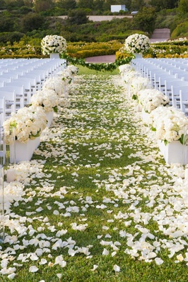Short white boxes filled with ivory floral arrangements