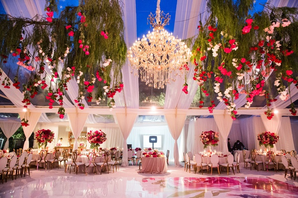 tent wedding reception watercolor dance floor chandelier roses hanging from trees gold chairs
