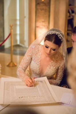 Bride in Reem Acra wedding dress with veil and long sleeves signing ketubah jewish wedding