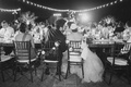 Black and white photo of bride and groom kissing at outdoor reception