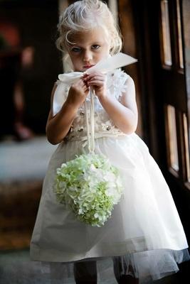 Flower girl holding hydrangea pomander ball