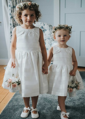two flower girls in white sleeveless dresses flower crowns baskets with pink roses white bow shoes