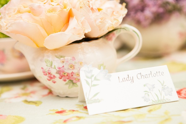 Escort card on bluebell design stationery with teacup in background