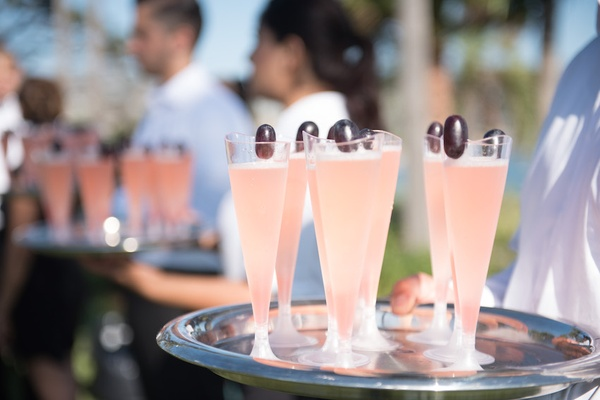 Light pink cocktail in Champagne glasses served at beachside wedding cocktail hour