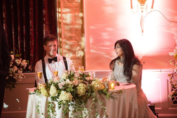 bride in elan, groom in armani without jacket, suspenders, newlyweds talk at sweetheart table