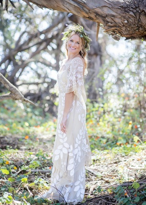 bohemian bride with unique dress leaf detailing floral garland crown in forest