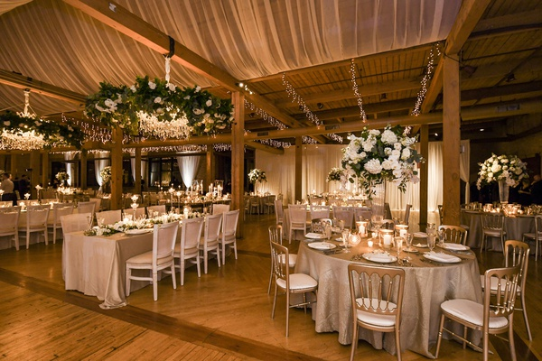 wedding reception long round tables chandelier flower garland tall centerpiece wood beams twinkle