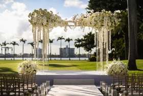acrylic wedding ceremony arch white orchid and cascading flowers rose hydrangea arrangements candles