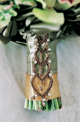 Stems of bouquet wrapped with ribbon and cascading jewel pendant
