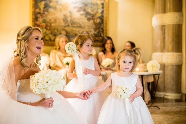 bride in monique lhuillier ball gown, holds hand of flower girl with pomador