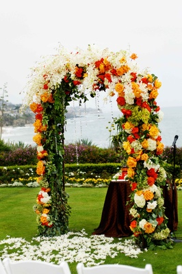 wedding arch with read orange and white florals and crystal details