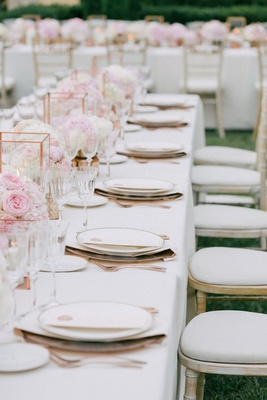 Wedding reception on grass lawn outdoor white chairs whitewash and long table pink flowers rose gold