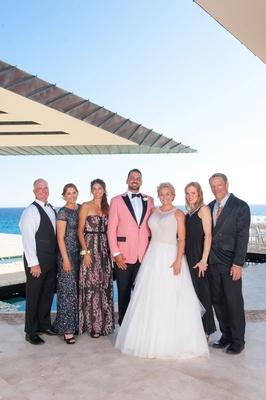 bride in mark zunino, groom in salmon suit jacket, family of the groom portrait, blended family