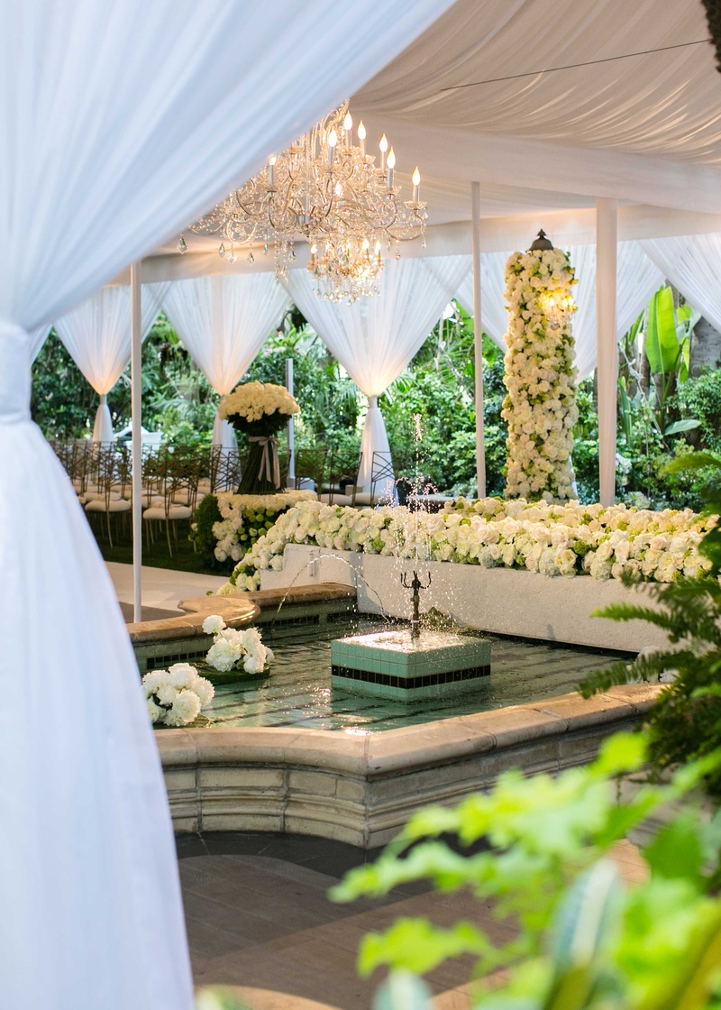 White drapes wedding ceremony space with fountain white rose greenery gold chairs
