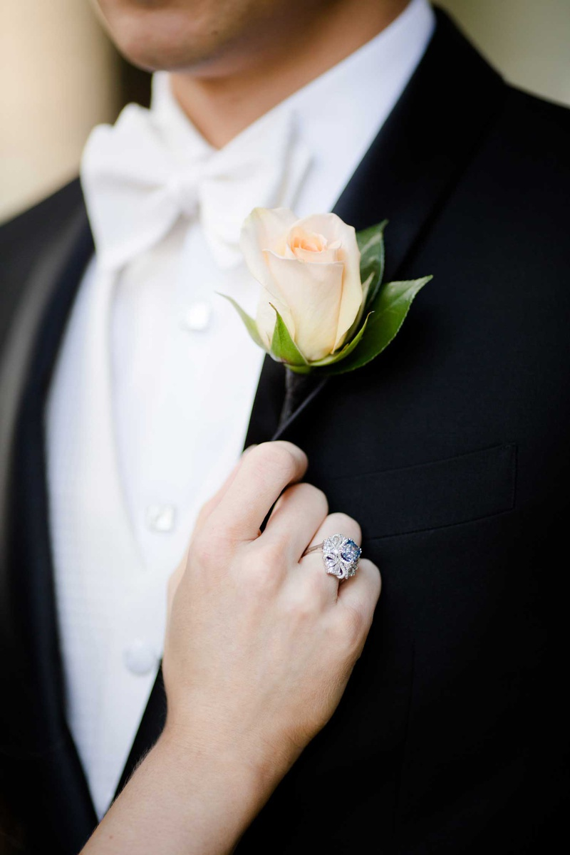 groom in white bow tie with peach pink rose boutonniere bride vintage blue silver engagement ring