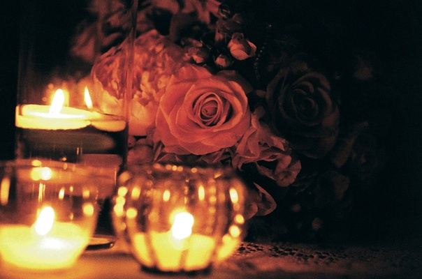 Rose arrangements next to floating candles at wedding