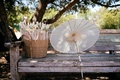 parasols handed out to guests for ceremony on wood bench