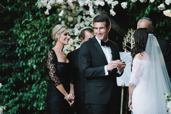 Mother of groom in black dress stands behind groom as he smiles with kiddush cup during ceremony