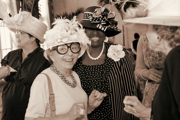 Sepia tone picture of tea party guests wearing hats