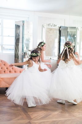 Three flower girls in tulle dresses white shoes flower crowns bows dancing on wood floor