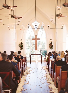 Chapel wedding church pews with cross and magnolia leaves on either side white flower petals floor