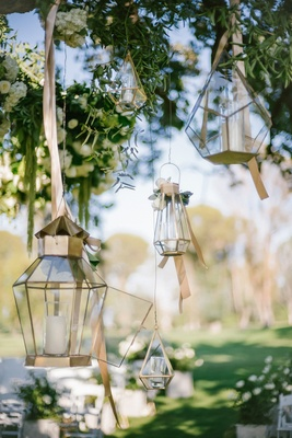 gold geometric lanterns with candles hanging from tree at outdoor wedding ceremony