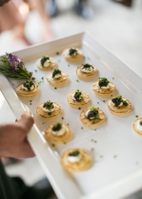 Ranch wedding cocktail hour with a tray of small pancakes, caviar, chives, cream