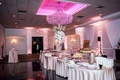 Wedding reception five tables with desserts and sweets under pink illuminated chandelier