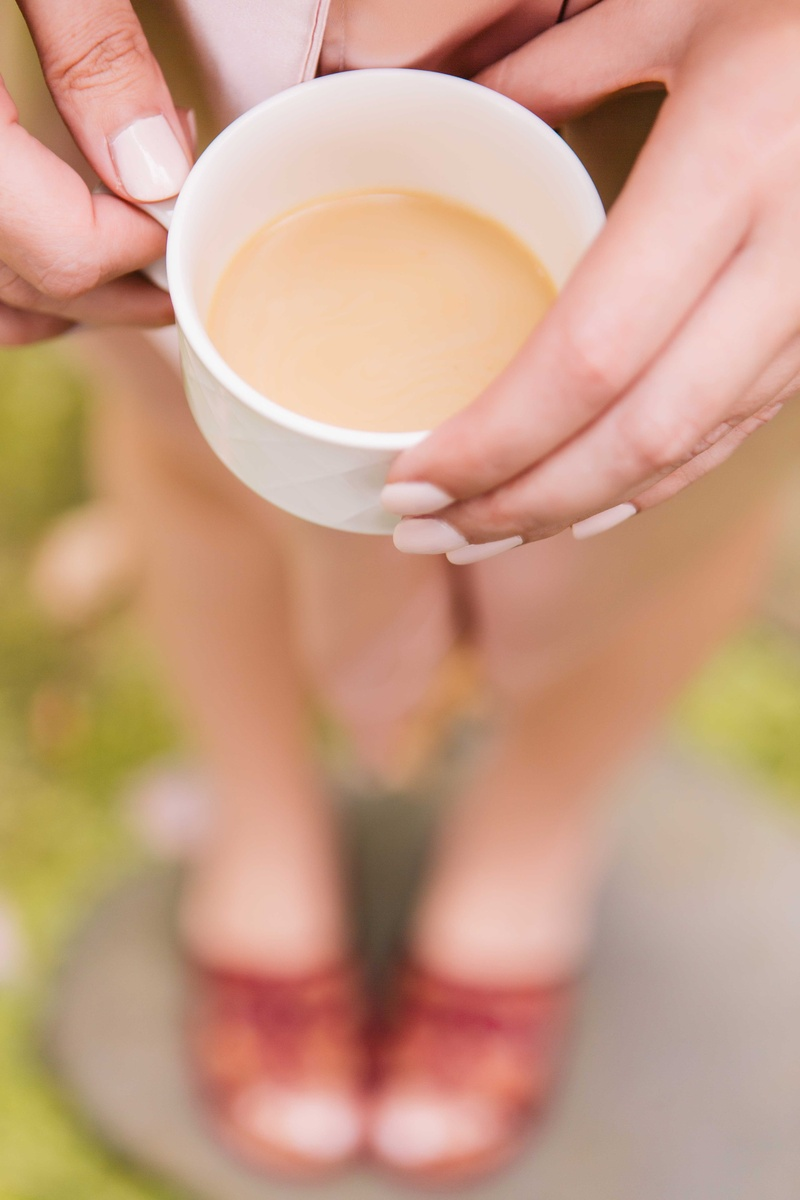 bridesmaid with cream painted nails displays a cup of coffee while getting ready