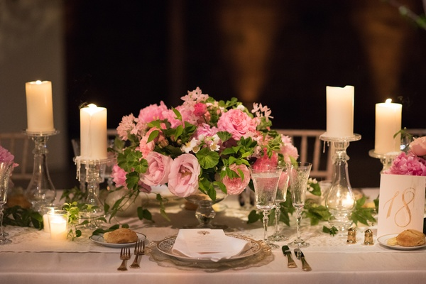 small arrangement of pink roses and greenery with pillar candles wedding reception centerpiece
