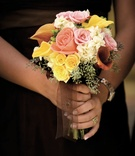 Bridesmaid's bouquet of pink, yellow, and white flowers