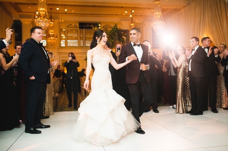 bride and groom holding hands and walking on dance floor guests watching chandeliers taking photos