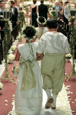 Little boy and girl walk down aisle