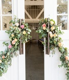 Large white barn farmhouse doors decorated with greenery pink rose yellow rose orange rose flowers