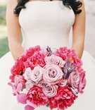 bride in white vera wang gown displays colorful bouquet pink and purple roses orchids