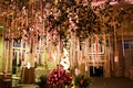 Wedding place card tree with white flowers and place cards hanging off the branches from ribbons