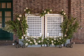 grey escort cards framed by gold and surrounded by greenery and white flowers