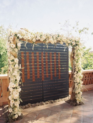 Wedding reception wood and white flowers greenery arch over dark wood and leather escort cards