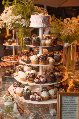 White multi-tiered stand with variety of cupcakes