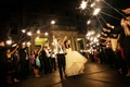 Bride in a Monique Lhuillier gown and groom in a black tuxedo at sparkler send-off