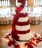 White wedding cake decorated with red roses