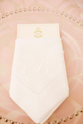 Clear charger plate with white napkin embroidered with initial