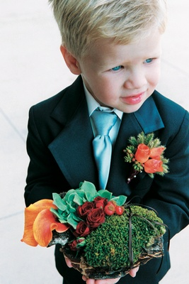 blonde ring bearer wearing blue tie and orange boutonniere carrying flower basket