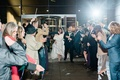 Send off for bride and groom grand exit wedding guests wave glow sticks confetti and streamers