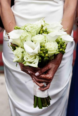 Bride with henna on hands holds white bouquet