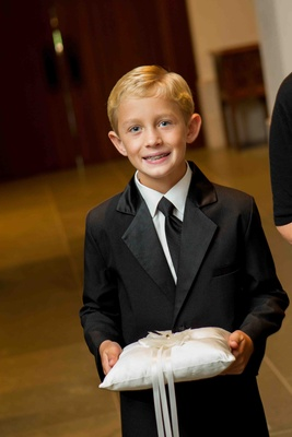 Blond ring bearer with black tie and braces